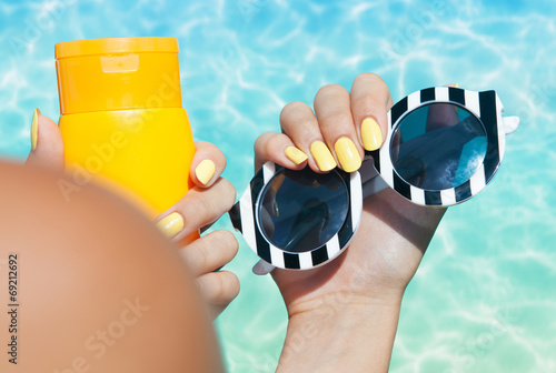 Woman holding sunglasses and sunscreen lotion at the pool - 69212692