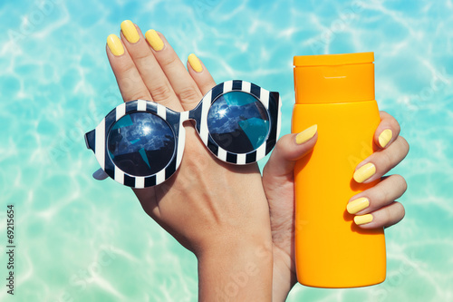 Woman at the pool holding sunglasses and sunscreen lotion
