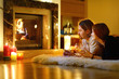 Happy couple by a fireplace on Christmas