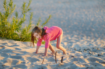 Adorable little girl playing on a beach
