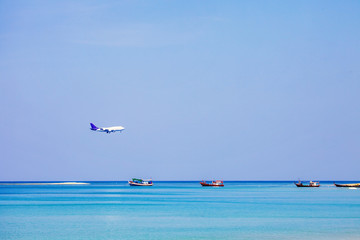 Boats in sea and airplane on blue sky