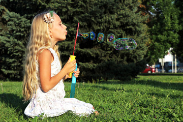 Girl in park blowing bubbles