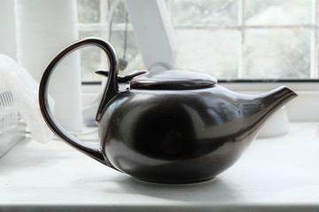 Brown asian teapot on the white windowsill