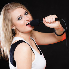 Girl singer singing to microphone on black