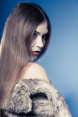 Portrait of girl with long hair. Young woman in fur coat