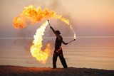 Fototapety Professional fire juggler performing on the beach