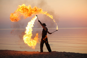 Professional fire juggler performing on the beach
