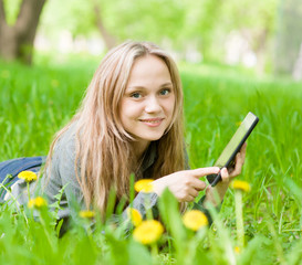 girl lying on grass with tablet computer and looking at camera