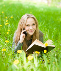 girl lying on grass with dandelions reading a book and talking o