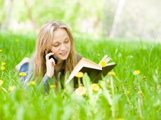 female student lying on grass reading a book and talking on the
