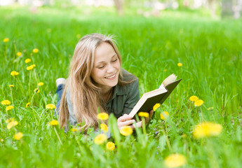 Pretty young woman lying on grass with dandelions reading a book