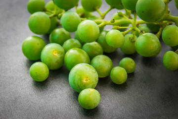 Unripe green grapes on dark background. Selective focus.