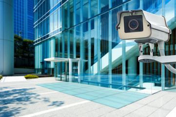 CCTV Camera or surveillance orperating with city building in bac
