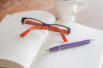 Pen and eyeglasses on notebook