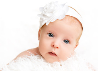 cute  newborn baby girl with a pink flower ribbon
