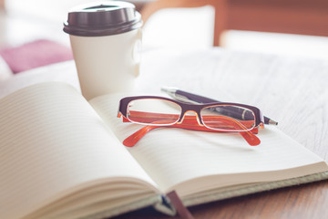 Eyeglasses with pen and coffee cup