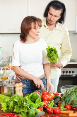 Happy young couple cutting the celery for salad in home kitchen