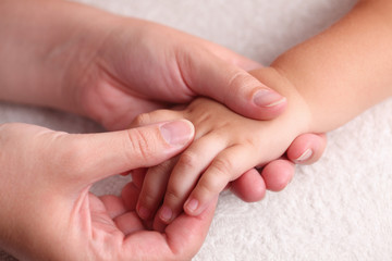 Mother massaging child's hand