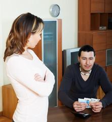 Man counting cash, woman watching him
