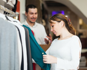 Girl and guy choosing clothes