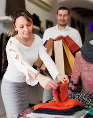 Smiling couple choosing clothes at store
