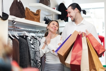 Young couple choosing clothes at boutique