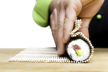 chef rolling up sushi
