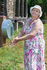 Smiling senior woman washing her hands outdoor