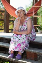 Elderly thoughtful Caucasian woman at summer veranda