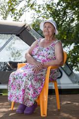 Joyous senior woman sitting on lake jetty