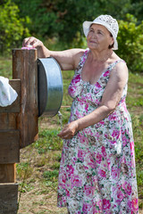 Elderly woman washing her hands with soap in washstand