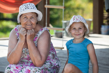 Smiling senior grandmother and happy grandchild sit on veranda