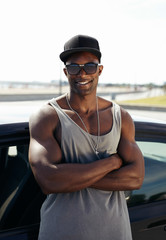 Stylised young muscular man leaning against car