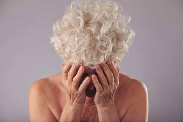 Sad senior woman on grey background