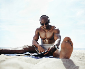 Young man sitting on beach reading a magazine
