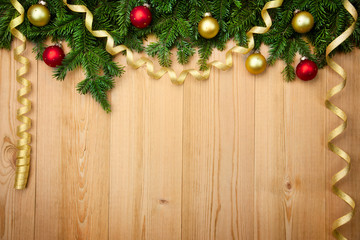 Christmas background with firtree, baubles and ribbons on wood