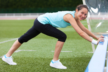 Young attractive woman stretching her leg