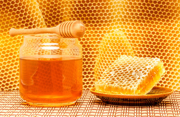 Honey in jar with dipper and honeycomb on mat