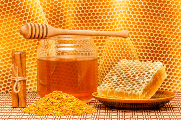 Honey in jar with dipper, honeycomb, pollen and cinnamon on mat