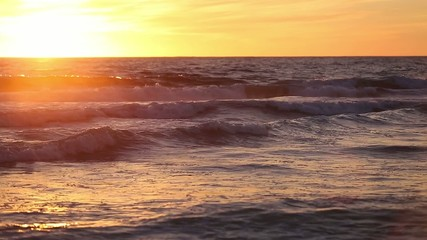 Evening sea waves at sunset in orange sunset