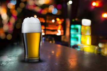 Glass of beer with bar scene in the background