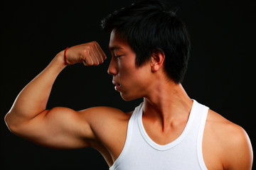 Asian fit man posing his muscles on black background