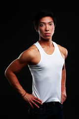 Portrait of a serious muscular asian man on black background
