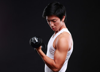 Asian man working out with dumbbells on black background