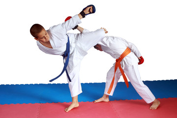 Boys are training blows karate on red and blue mat