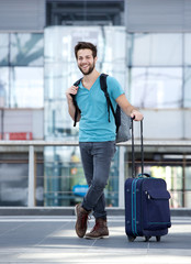 Young man smiling with bags at airport