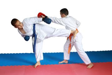 Two athletes in karategi are beating karate blows