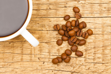 Coffee cup with roasted coffee beans on table - view from top