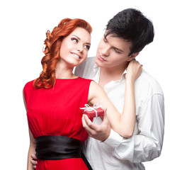 young smiling couple holding small red gift