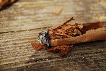 rozerwane cygaro, które się pali na drewnie - deskach